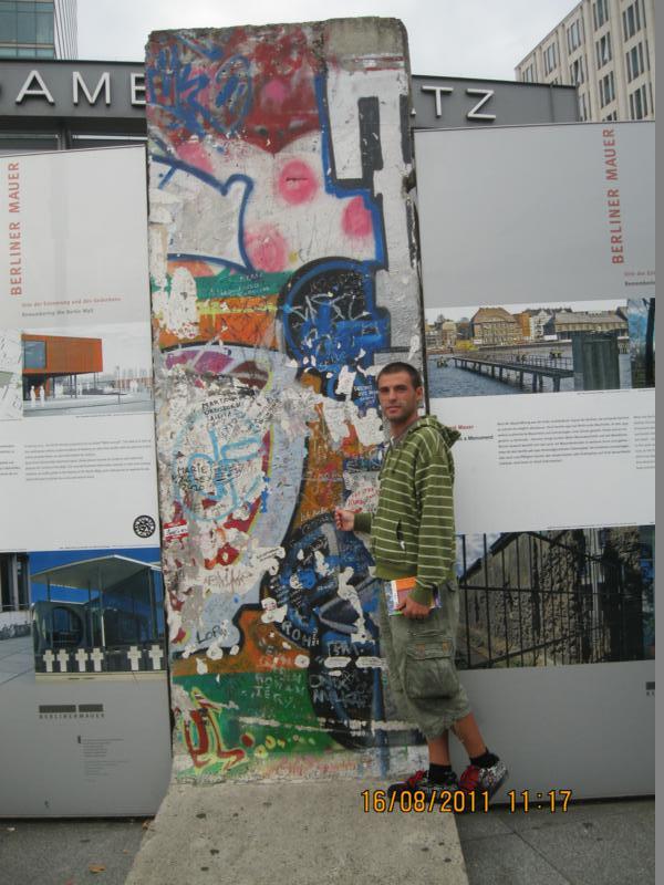 Junto a un trozo del Muro de Berlin .
